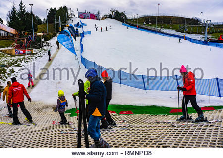 Poznan, Poland - February 10, 2019: Kids and instructors waiting in a line to climb up the ski training track at the Malta park on a cold winter day w - Stock Image