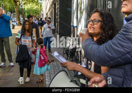 London, UK. 10th August 2018. A woman reads out the petition which campaigners are about to hand to the Bangladesh High Commission in London,. The protest by relatives and friends, incuding several well-known photographers, called for the immediate release of Shahidul Alam, seized from his house by police on Sunday shortly after he gave an interview to Al Jazeera over Skype on the road safety protests in Bangladesh. Credit: Peter Marshall/Alamy Live News - Stock Image