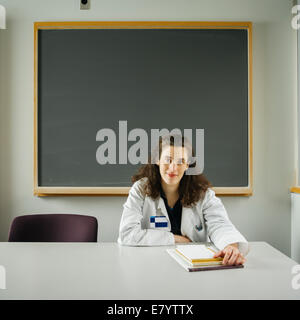 Woman at classroom desk with chalkboard in background - Stock Image