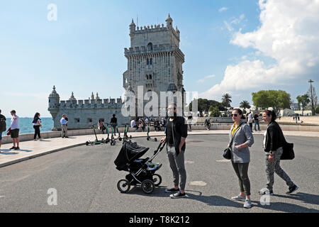 Man hipster with beard pushing baby in pram visiting Belem Tower with women family tourists outside building in Belem Lisbon Europe  KATHY DEWITT - Stock Image