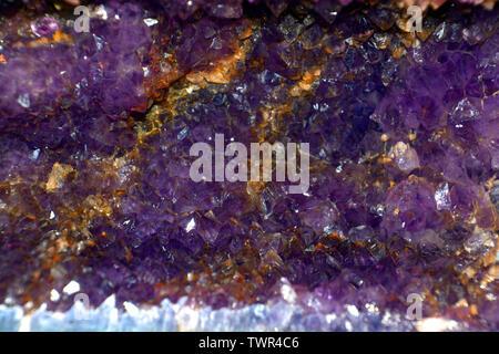 deep violet amethyst geode close up view, amethyst quartz natural crystal gemstone macro shot purple background with bokeh effect - Stock Image