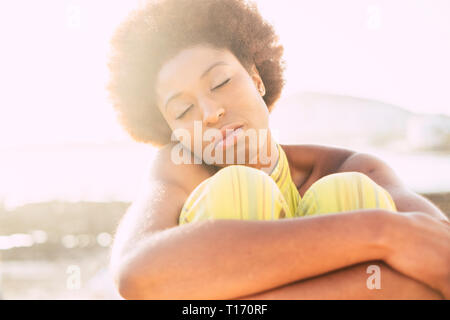 Lonely cute afro american hair style girl sitting and hugging herself in outdoor feeling the nature and sensations around - portrait of young black gi - Stock Image