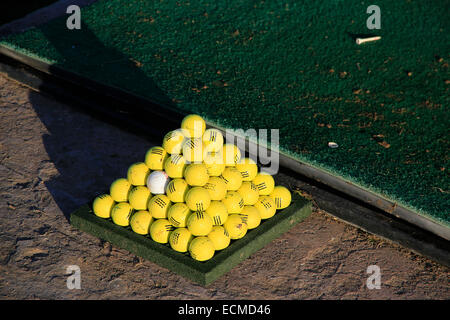 Tropical golf driving range with golf balls stacked in pyramids. - Stock Image