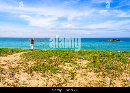 Woman staring out to sea on a beach in Phang Nga, Thailand - Stock Image