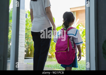 Mother holding hand of little daughter with backpack and kindergarten school uniform - Stock Image