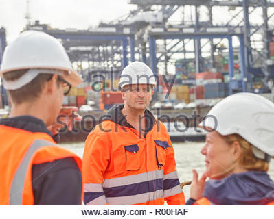 Dock manager and supervisor instructing worker to move cargo containers infront of ship - Stock Image