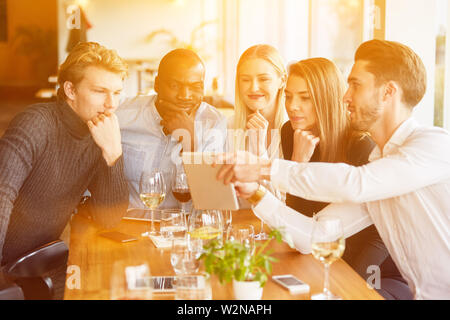 Group at meeting in restaurant looks together on tablet computer - Stock Image