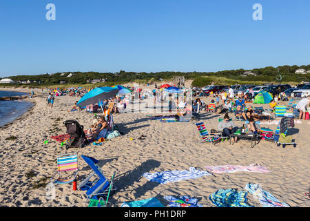 People gather and wait on Menemsha beach to view the sunset over the Vineyard Sound in Chilmark, Massachusetts on Martha's Vineyard. - Stock Image