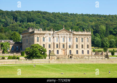 Chatsworth House park with people walking across the grass in parkland and woods Derbyshire England UK GB Europe - Stock Image