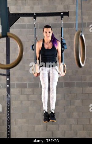 Young woman athlete doing muscle up exercises on rings during her workout in the gym in a full length frontal view raised on extended arms - Stock Image