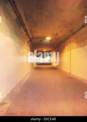 Silhouette of two men walking through an underpass tunnel. Vintage paper texture overlay. - Stock Image