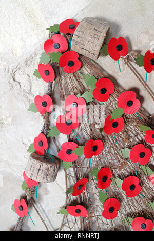 A fishing net adorned with red poppies in the parish Church of the Holy Trinity and All Saints at Winterton-on-Sea, Norfolk, England, UK, Europe. - Stock Image