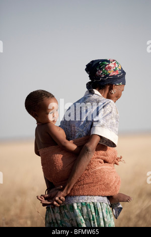Botswana, Makgadikgadi, A bushman mother carries her child - Stock Image