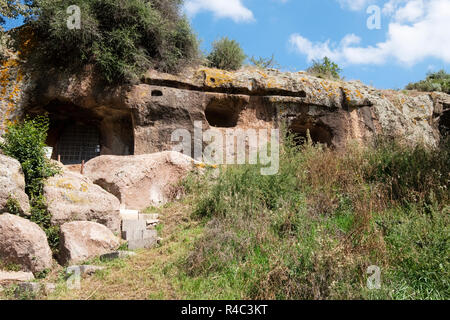 Domus de Janas, 'houses of the fairies'. Neolithic hypogeal tombs, volcanic rock (trachyte}. Necropolis Sant' Andrea Priu complex. Bonorva, Sardinia - Stock Image