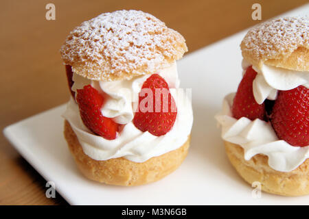 Whipped cream and strawberries puffs - Stock Image