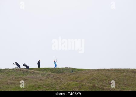 Camber, East Sussex, UK. 15th Apr 2019. On a warm and hazy day at Camber Sands, Golfers play a round of golf at the Rye golf club, built on top of the many sand dunes along this part of the coast. ©Paul Lawrenson 2019, Photo Credit: Paul Lawrenson/Alamy Live News - Stock Image