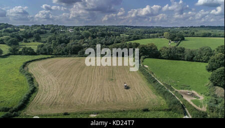 Aerial view of a tractor working on a field in the English countryside - Stock Image