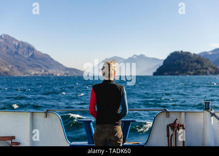Italy, Como, rear view of woman on the ferry enjoying the view of Lake Como - Stock Image