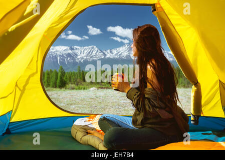 Young woman cup mountains tent - Stock Image