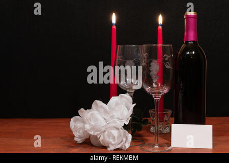Beautiful etched wine glasses and bottle of red wine, red candles and white roses on wooden table with name tag on dark background. Valentines, Mother - Stock Image