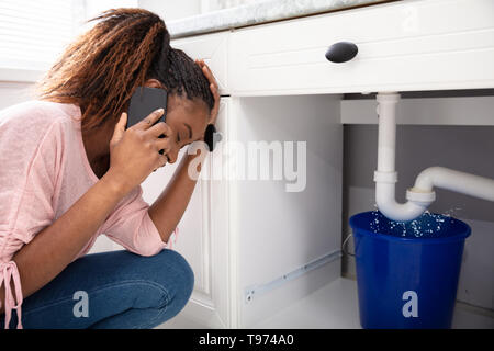 Young Woman Calling Plumber Crouching In Front Of Water Leaking From Sink Pipe - Stock Image