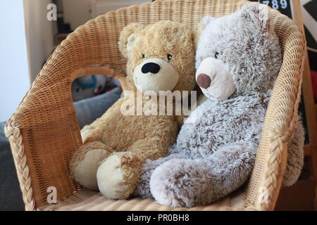 two teddy bears sitting together on a wicker chair - Stock Image