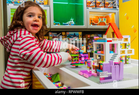 baby child girl play with Lego bricks inside the Lego Store - Stock Image