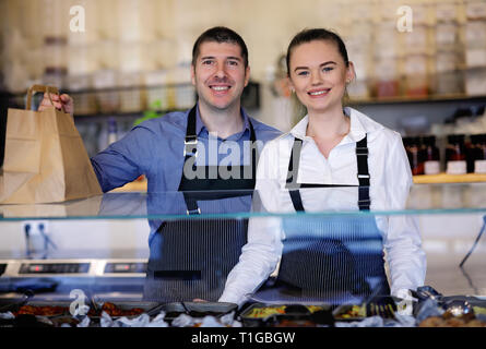 Young man and woman standing behind the counter of a restaurant. Kitchen behind - Stock Image