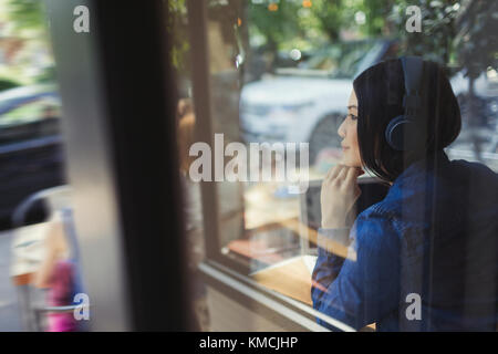 Pensive young woman listening to music with headphones looking away at cafe window - Stock Image