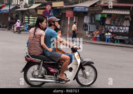 A Vietnamese man with his wife and son riding on a moped on a street past shops, Hanoi, Vietnam - Stock Image