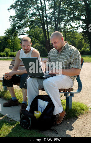 Two men with a laptop sit on a bench at the Alster in Hamburg, Germany, June 2006. Photo: Jens Schierenbeck - Stock Image