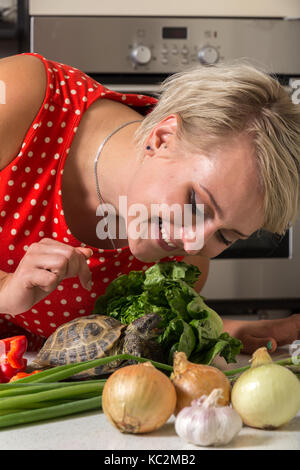 Cute girl smiling and watching over tortoise - Stock Image