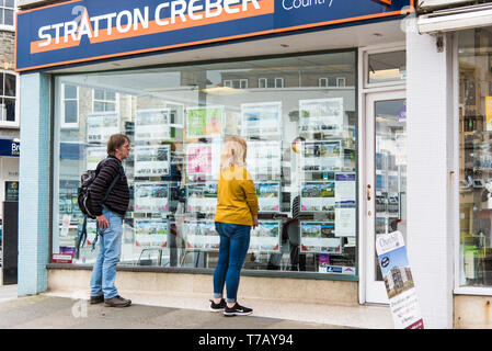 People looking at property information in a Stratton Creber Estate Agent window in Newquay Town Centre in Cornwall. - Stock Image