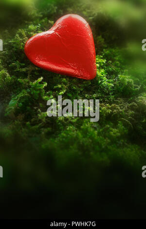 Chocolate heart in bright red foil wrapper on dark green moss. Romantic background texture with plenty text or copy space - Stock Image