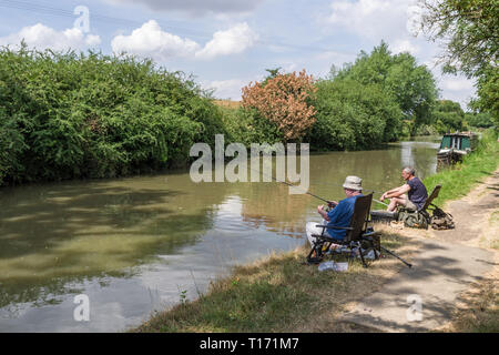 Two male friends, sitting side by side, fishing on the Grand Union canal, Blisworth, Northamptonshire, UK - Stock Image
