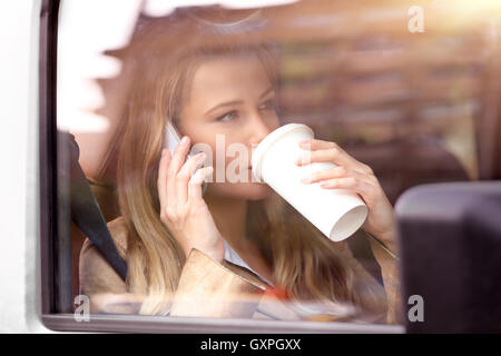 Portrait of a beautiful business woman sitting in the car with cup of coffee, talking on the phone - Stock Image