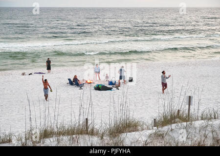 Florida, USA, beach with a family or people playing around a campfire along the Florida gulf coast or panhandle near Destin in late evening or sunset. - Stock Image