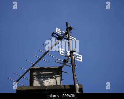 TV aerials  attached to a chimney on the roof - Stock Image