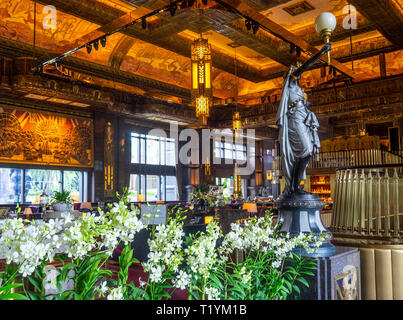 Bronze sculpture or statue with light fitting at entrance to Atlas bar in the lobby of Parkview Square Singapore. - Stock Image