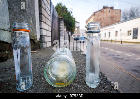 three abandoned empty bottles on the street of Warsaw, Poland, blurred background, no people. - Stock Image