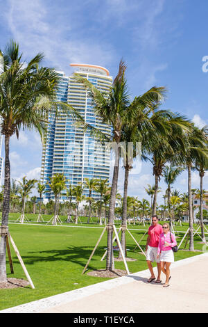 Miami Beach Florida South Pointe Park Grand Reopening event grass field landscaping pedestrian walkway man woman couple strollin - Stock Image