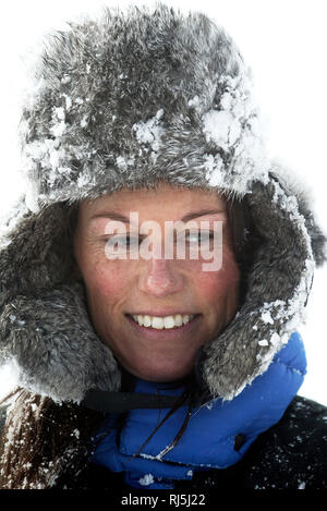Woman in a snowy fur cap - Stock Image