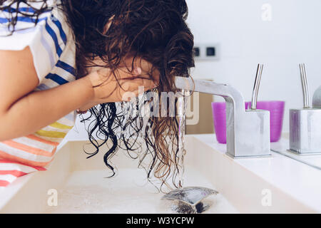little girl washing her face with water in the bathroom at morning after shower, kids hygiene concept - Stock Image