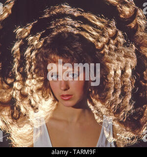 Young female model posing for 1980s experiment with zoom lens & flash lighting for surreal hair style portrait photography technique studio England UK - Stock Image