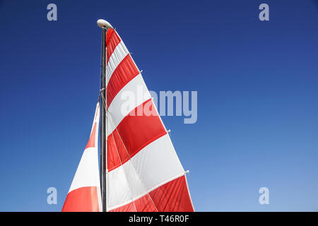 Sailing boat with red sail on a beach - Stock Image