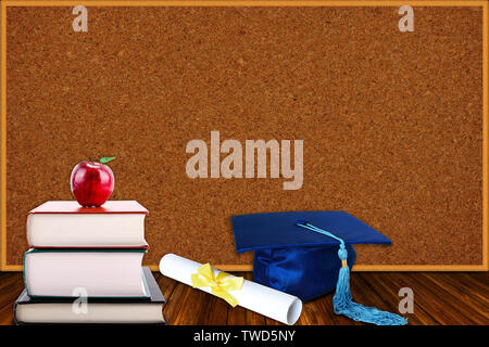 Education concept with blue graduation hat and diploma and stack of books with apple on cork board background. Copy space on corkboard. - Stock Image