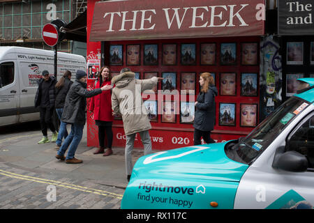 A passer-by offers directions to a couple on the street corner of Berwick and Broadwick Streets on 5th March 2019, in London, England. - Stock Image