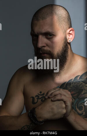 Portrait tough man with beard and tattooed chest, making fist - Stock Image