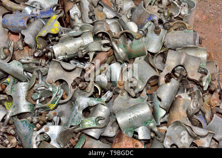 Pile of scaffolding coupler clamps on the ground used on a building site in UK - Stock Image