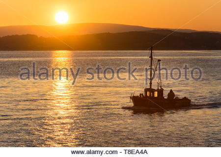 Morecambe, Lancashire, UK, 13 May 2019, UK Weather. Sunrise over Morecambe Bay as one of the last shrimpers operating out of Morecambe heads out to the shrimping grounds as high tide approaches. After a cold night, unbroken sunshine is forecast  for the start of the working week and temperatures in the low 70s Fahrenheit may be reached in North West England by the middle of the week. Credit: Keith Douglas News/Alamy Live News - Stock Image